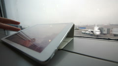Using tablet PC on windowsill at the airport Stock Footage