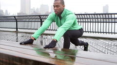 A man leans on a bench and stretches his legs in prepartion for going on a run Stock Footage