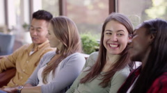 Happy friends hanging out at home. 1 young woman turns to smile at camera - stock footage