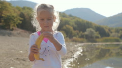 Little beautiful girl stands near a lake, cleans banana and starts eating it Stock Footage