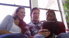 Cheerful group of young friends hanging out together with computer tablet - stock footage