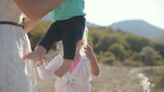 Mom gives the baby in his arms of eldest daughter Stock Footage