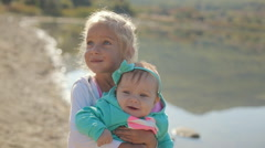 Older sister holds on hands junior near the lake - stock footage