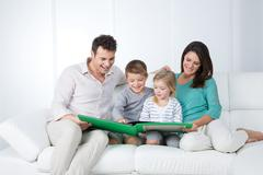 Parents reading with their children Stock Photos