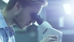 Engineer Inspects Detail Quality under Microscope on Factory - stock footage