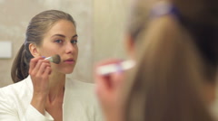 Pretty woman applying make up Stock Footage