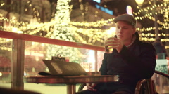 A young adult enjoying his beer on a terrace in december with christmas light - stock footage
