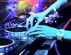 dj mixes the track in the nightclub at a party. in the background laser light - stock photo