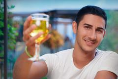 Young Man Rising a Glass in a Bar Stock Photos