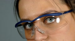 A woman wearing protective glasses. Close up view Stock Footage