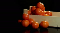 slider shot of group of mandarins in wooden crate standing on black background - stock footage