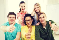 Smiling students at school showing thumbs up Stock Photos