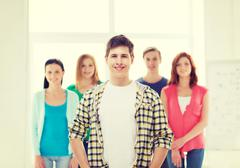 smiling male student with group of classmates - stock photo
