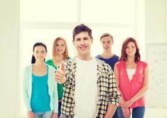 Male student with classmates showing thumbs up Stock Photos