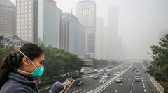 In the bad weather,the lady with mask takes photo of buildings in Guomao CBD Stock Footage