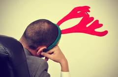 Man with a reindeer antlers headband in his office chair, with a filter effec Stock Photos