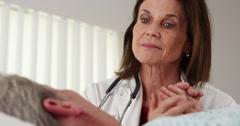 Senior doctor comforting elderly patient's hand - stock footage