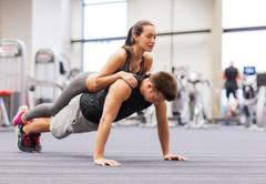 Smiling couple doing push-ups in the gym Stock Photos