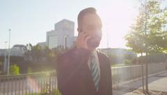 CLOSE UP: Smiling businessman talking on the phone in morning - stock footage
