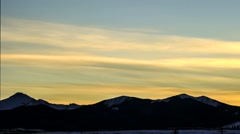 Timelapse clip of orange skies and snowy mountain ridge Stock Footage