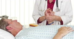 Doctor holding patient's hand and comforting him Stock Footage