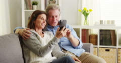 Senior couple using smartphone on couch Stock Footage