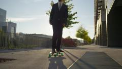 SLOW MOTION: Cool young businessman skateboarding to work - stock footage