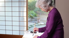 Senior Asian Woman Practices Calligraphy - Side View Stock Footage