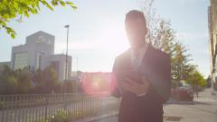 SLOW MOTION: Worried businessman checking news on digital tablet outdoors Stock Footage
