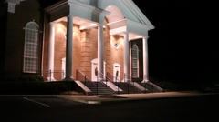 car drives by front of church lighted at night - stock footage