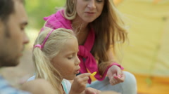 Wonderful family blowing soap bubbles while relaxing on nature Stock Footage