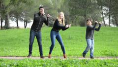 Young couple and child dancing in a park - stock footage