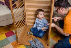 Father and son assembling cot for a newborn at home - stock photo