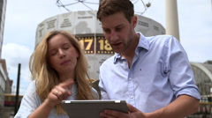Young couple discussing with tablet in front of Work Clock, Berlin, Germany Stock Footage