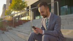 CLOSE UP: Happy businessman browsing the internet on his smartphone Stock Footage