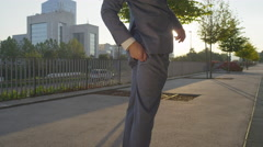 SLOW MOTION: Businessman ripping his pants to pick up papers Stock Footage