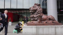 Employee members walk past a sculpture of lion of HSBC bank Stock Footage