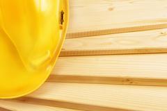 Stock Photo of yellow hardhat on pine wood planks