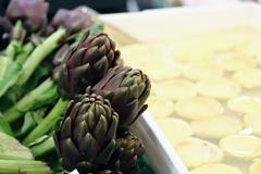 Artichokes for sale in stand of greengrocers to local market Stock Photos