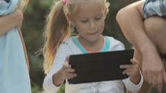 Close up of little curious girl with tablet sitting with her family - stock footage