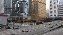 Vehicles run along office buildings in Hong Kong Central Stock Footage