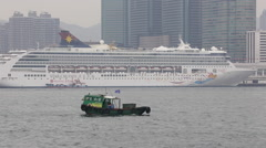 A fish boat pasts a cruise ship parking at Victoria Harbour Stock Footage
