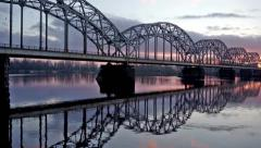 Train rides on fishnet bridge over the river at sunset Stock Footage
