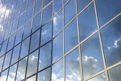 reflexions of clouds and  sky in facade of modern building - stock photo