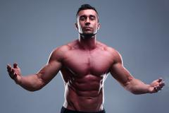 Portrait of a muscular man with nice abs over gray background Stock Photos