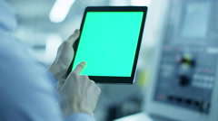Worker is Using Tablet PC with Green Screen in Portrait Mode - stock footage