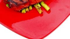 Rare medium roast beef fillet asparagus served on red dish Stock Footage