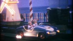 1409 - children drive miniature car at amusement park -vintage film home movie Stock Footage