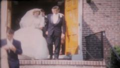 1406 - newlyweds walk out of the church after ceremony -vintage film home movie  Stock Footage