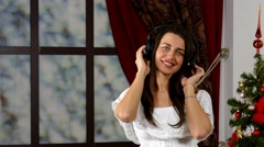 Woman listening pop music via headphones Stock Footage